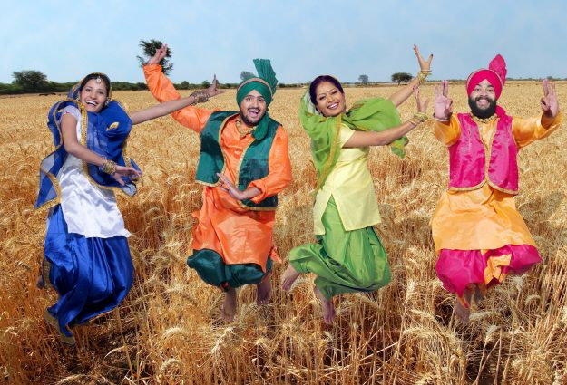 Image of Bhangra dancers in a corn field - could be in Norfolk or the Pubjab, as they have similar landscapes